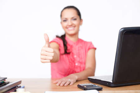 beautiful young business woman sitting at office desk and hand make thumbs up photo