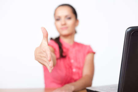 beautiful young business woman sitting at office desk and extending hand to shake Stock Photo - 10876434