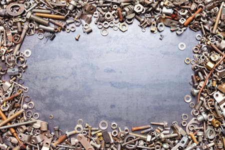 close fitting: assorted nuts and bolts frame on metal texture background