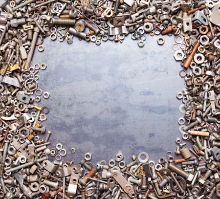 metal fastener: assorted nuts and bolts square frame on metal texture background