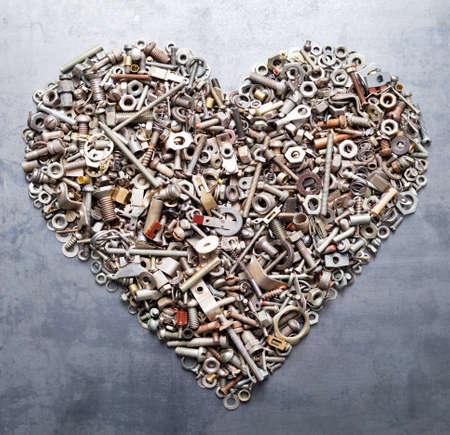 herramientas de construccion: una variedad de frutos secos y el corazón de los pernos de metal sobre fondo de textura Foto de archivo