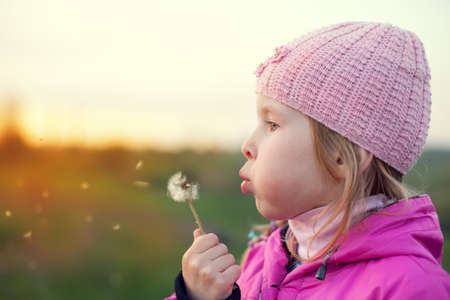 little girl in cap with dandelion at sunset in autumn photo