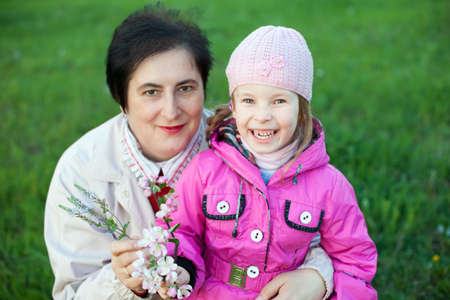 mature woman and funny little girl with branch of apricot flowers on green grass background photo
