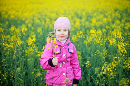 little girl with flower in field of yellow flowers photo
