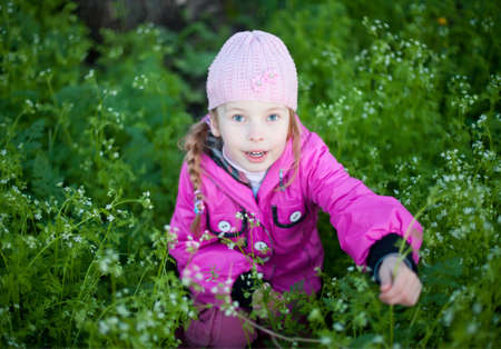 little girl in cap collects flowers photo
