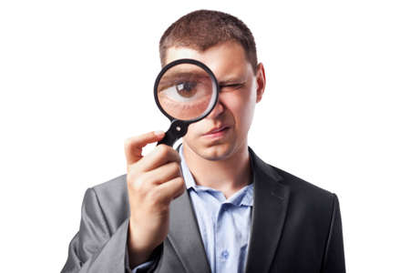 man face close up: businessman in a suit looking through a magnifying glass isolated on white background