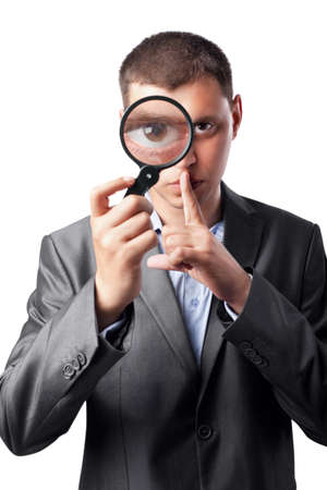 businessman in a suit looking through a magnifying glass isolated on white background photo