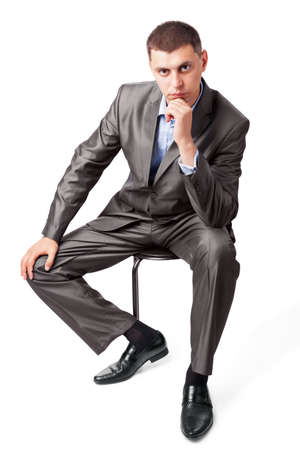 style advice: confident business man portrait sitting on a chair isolated on white background