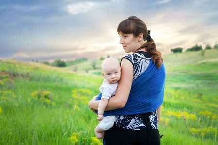 mother and son in sling on green meadow at sunset in the summer  photo