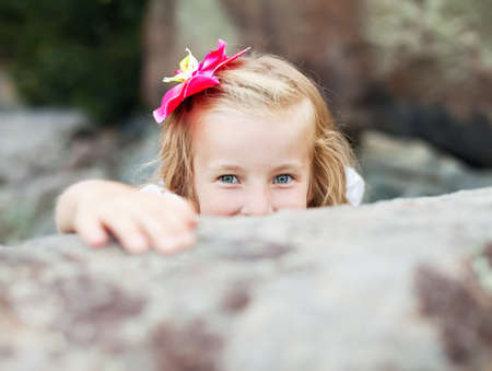 gray eyes: beautiful blonde little girl girl hides behind a stone