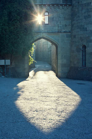Light falling through an arch and lock window. Mysterious urban scene. Ancient street.  Stock Photo