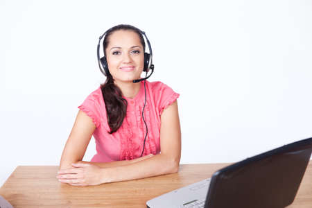 call center female operator. young happy smiling woman sitting at office desk with headset isolated on white background. Stock Photo - 10876409