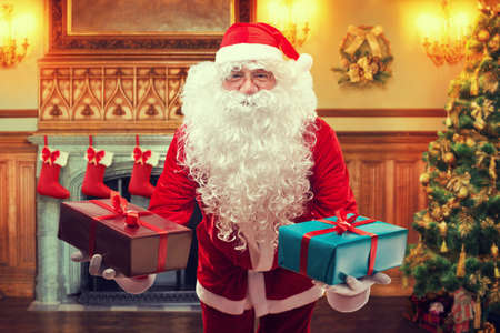 Santa Claus with gifts in decorated living room photo