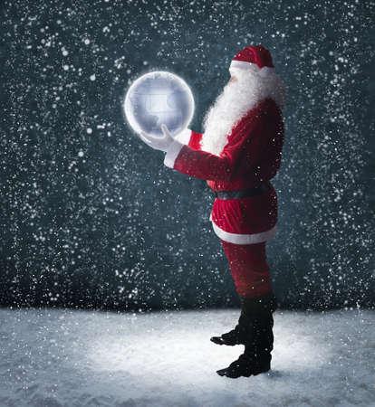 happy planet earth: Santa Claus sosteniendo el planeta tierra brillando bajo la nieve que cae