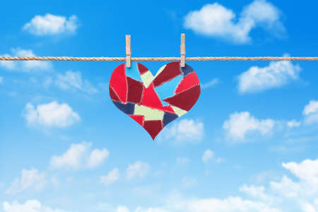 flap:  fabric scraps heart hanging on clothesline against sky