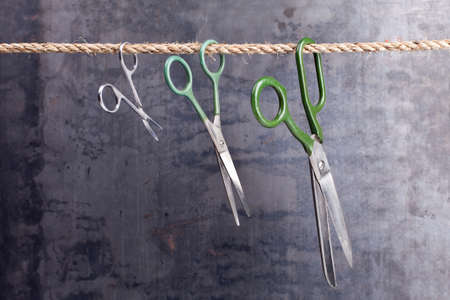 Three scissors hanging on a rope on grunge texture photo