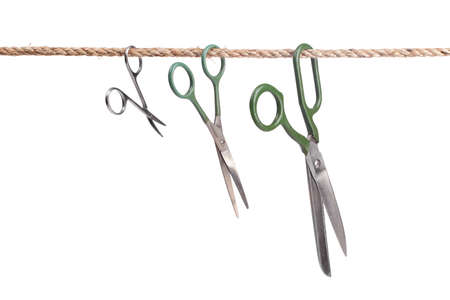 Three scissors hanging on a rope isolated on white background  photo