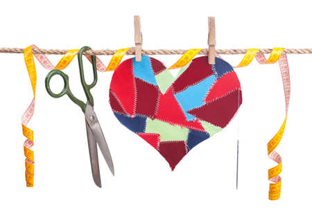 fabric scraps heart and sewing accessories hanging on the clothesline. Isolated on white. Valentines Day
