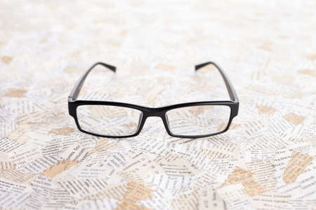 opthalmology: reading glasses on paper background  Stock Photo