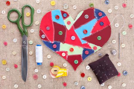 Accessori da cucire e tessuti cardiaci scarti su sfondo trama del tessuto. Valentine