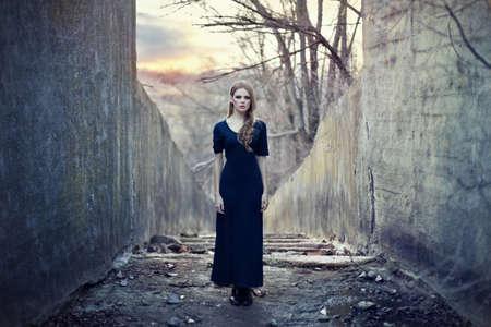 bella ragazza sola in abito lungo vicino tunnel cupo sul tramonto