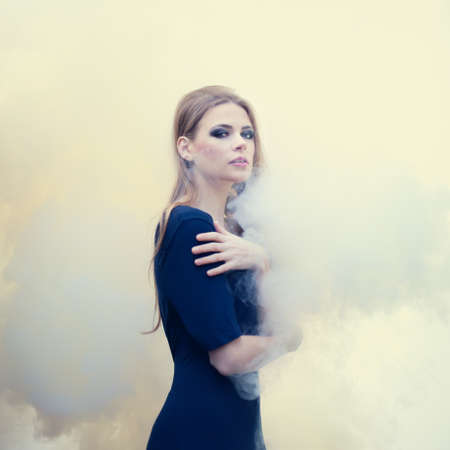sensual beautiful girl in white smoke on nature photo