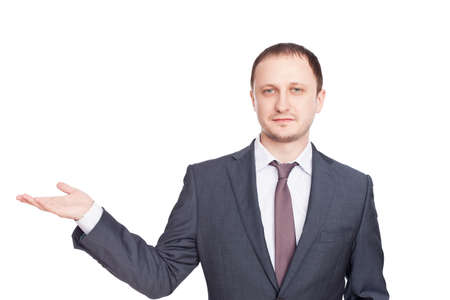 Young businessman in a suit presenting something isolated on white background photo