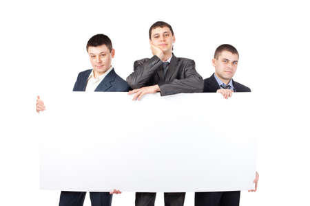 Three young businessmen hold up a large blank sign isolated on white background photo