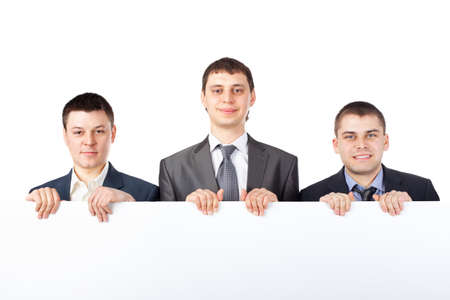 hold up: Three young businessmen hold up a large blank sign isolated on white background