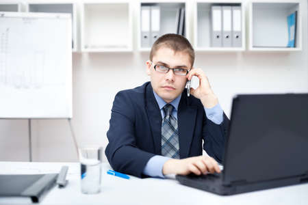Portrait of young business man talking on cell phone and working on a laptop at office photo