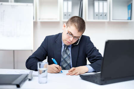 Portrait of young business man in the office doing some paperwork and talking on cell phone photo