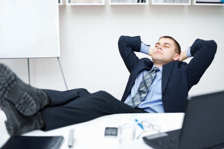 Tired businessman sleeping on chair in office with his legs on the table  photo