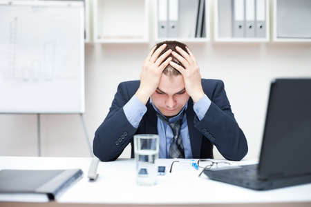 Depressed young business man holding his head at office photo