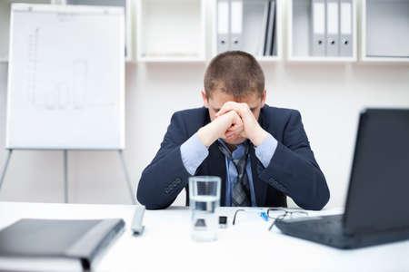 Jeune homme d'affaires avec des problèmes et le stress au bureau Banque d'images