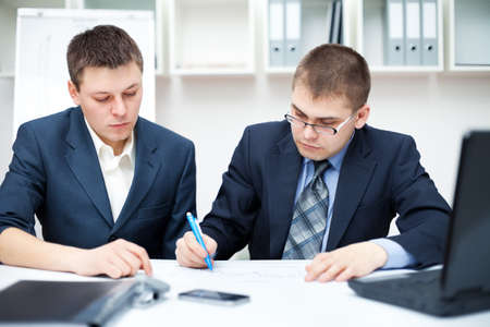 Two young business people sitting at desk working in team together, working with documents sign up contract  photo