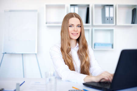 busy  office: Portrait of beautiful young smiling business woman working on a laptop at office Stock Photo