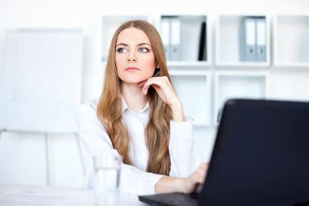Portrait of beautiful young pensive business woman working on a laptop at office photo