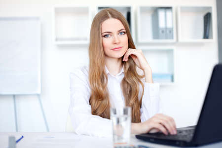 Portrait of beautiful young smiling business woman working on a laptop at office photo