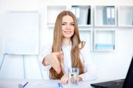 Portrait of beautiful young smiling business woman sitting at desk offering a handshake in bright office photo