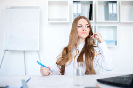 Portrait of a beautiful young business woman working in bright office Stock Photo - 14459874