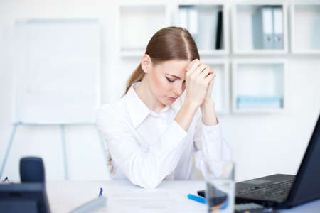 Tired young business woman in bright office photo