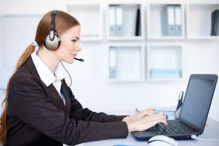 Ritratto di giovane donna bella operatore seduto alla scrivania ufficio con auricolare