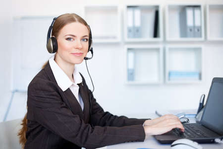 Portrait of pretty young female operator sitting at office desk with headset Stock Photo - 14459851