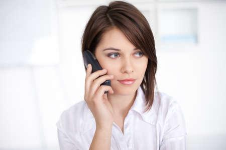 Chân dung chụp gần của thành công xinh đẹp người phụ nữ doanh nghiệp trẻ nói về cuộc gọi điện thoại tại văn phòng