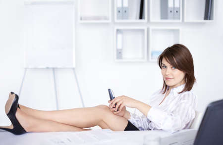 beautiful young smiling business womanl with legs on desk at office  photo