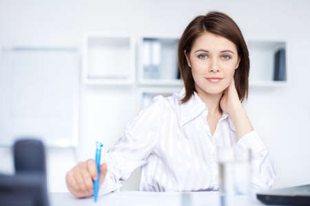 desk work: Closeup of relaxed young  beautiful young business woman smiling at office  Stock Photo