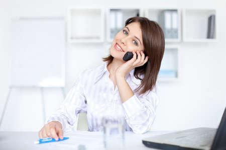 Closeup của thành công xinh đẹp người phụ nữ doanh nghiệp trẻ nói về cuộc gọi điện thoại tại văn phòng