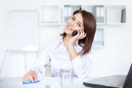 Closeup of successful beautiful young business woman speaking on phone call  at office photo