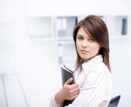 portrait of beautiful young business woman holding folder at office