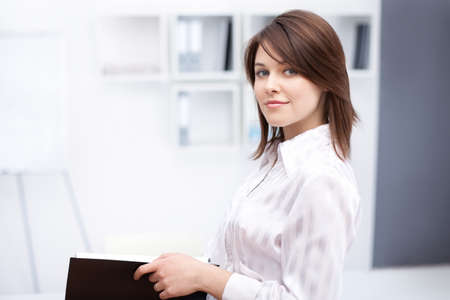 young professionals: portrait of beautiful young business woman holding folder at office